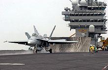 Chasseur F/A-18 sur le pont d'envol, prêt au catapultage.