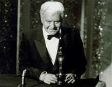 A black-and-white image of a smiling white-haired elderly man wearing a tuxedo stands in front of a podium holding a shining statue of a man.