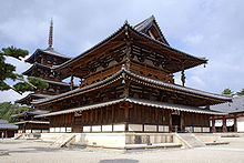 A large wooden building with a hip-and-gable main roof and a secondary roof giving the impression of a two-story building. Between these roofs there is an open railed veranda surrounding the building. Below the secondary roof there is an attached pent roof. Behind the building there is a five-storied wooden pagoda with surrounding pent roof below the first roof.