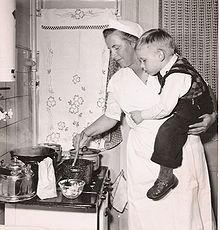 une femme qui cuisine avecun enfant dans les bras