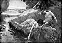 Deux fées se prélassent sur l'herbe en bordure d'un cours d'eau.