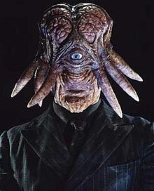 Portrait image of an alien creature with a vertically elongated head, small mouth, prominent chin and large exposed brain. A single grey eye is set centrally in the face, with tentacles protruding from the sides of the head. It wears a black shirt, tie and black pinstripe jacket.