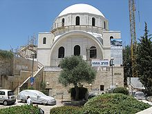 A building covered in shimmering white Jerusalem stone stands against a backdrop of a clear blue sky. A bright white dome roof, supported by a bricked parapet including several arched unglazed windows, sits above a stone arch. The stone arch spans the width of the building and three arched unglazed windows lie below it. They are flanked by two towers on either side. Scaffolding is fixed around various parts of the external structure, with a scaffold staircase to the left of the building and the tall latticed boom of a tower crane on the right. The construction company's promotional hoarding can be seen affixed to the right side of the building.