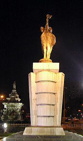 A stone statue of torch-bearers as seen at night. A fountain with a white base is in the background