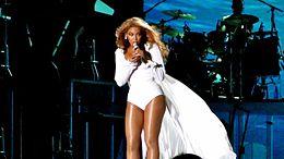 Cette image nous présente une femme brune afro-américaine portant un justaucorps blanc avec une traîne blanche derrière. Ses cheveux sont en mouvement et elle porte des boucles d'oreilles. Elle tient un microphone qu'elle porte à sa bouche avec ses deux mains. Au fond, il y a un écran de couleur bleu avec devant une batterie et une femme derrière cette batterie.