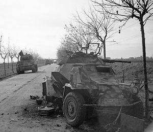 Sherman tanks passing a disabled German armoured car