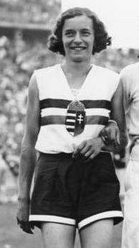 A black and white photograph of a female athlete with short cut hair. She wears a white sleeveless top with two horizontal stripes and a crest in the middle of her chest, and dark shorts.