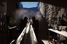 Deux hommes dans une fosse préparant un long tube métallique reposant sur une gouttière