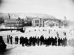 Photo noir et blanc d'un match de hockey joué en extérieur devant une ville enneigée.
