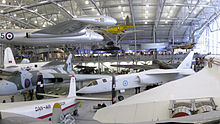 Various aircraft, large and small, exhibited in a hangar.