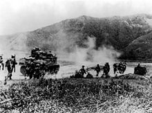 Image of Gurkhas advancing alongside M3 Lee tanks towards foothills in the distance