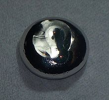 A flattened drop of dark gray substance.