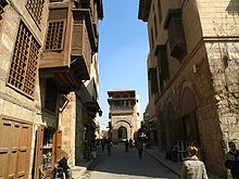Several people walk down a small empty lane overshadowed on both sides by three-story buildings with shrouded balconies and windows of Islamic style