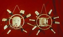 Photo of 2 masks. In the center is the image of a face, surrounded by a ring, in turn surrounded by 8 white rectangular pieces