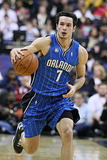 """A fair-skinned man is dribbles a basketball. He is wearing a blue basketball uniform with the word """"ORLANDO"""" on the jersey."""