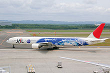 A Boeing 777300 aircraft with special Oneworld livery taxiing from the tarmac on to the taxiway, with a mountain view on the background
