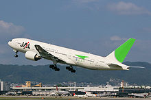A Boeing 777200 aircraft in mid air during take-off, with the view of Itami Airport in the background