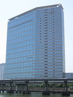 "A modern multi-storey building in blue and grey colour, with Japan Airlines&squot; ""JAL"" logo on the top right, there are blue sky on the background and a highway bridge in the foreground"