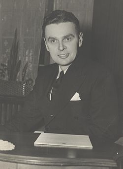 Diefenbaker, with a pleased expression on his face, sits at a desk, before him is a pile of House of Commons stationary.