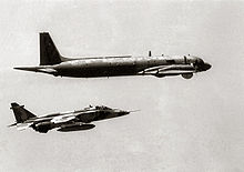 Black-and-white photography of jet aircraft, carrying external fuel tank under fuselage, accompanying behind a four-turboprop-driven aircraft.