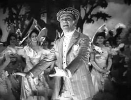 Cagney on stage and in costume, singing and dancing while the cast watches.