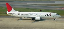 A Boeing 737400 aircraft painted in Japan Transocean Air livery, travelling along the runway during take-off, with a clear green grass strip in the foreground and a blue sea view in the background