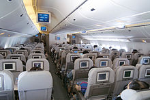Inside view of an aircraft's Economy Class cabin with television on the back of the seats and overhead lockers on the ceiling
