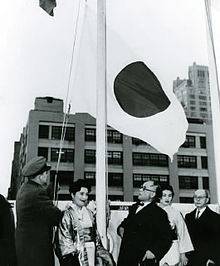 A group of men and women watching a flag being raised.