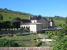 La photo couleur représente un château devant lequel s'étend un jardin à la française. En arrière-plan, le coteau est couvert de vignes.