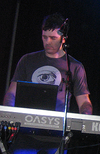 Upper body shot of a 34-year-old man. He is partly obscured by a keyboard and microphone in front of him. He has short dark hair and wears a dark tee-shirt which has a large open eye logo. His eyes are directed down and slightly to his right. His arms are raised to the keyboard but his hands are obscured. The lettering O-A-S-Y-S is visible on the back of the synthesiser with an additional K at the right.