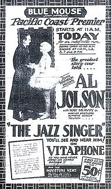 "Advertisement from the Blue Mouse Theater announcing the Pacific Coast premiere of The Jazz Singer, billed as ""The greatest story ever told"". A photo of stars Al Jolson and May McAvoy accompanies extensive promotional text, including the catchphrase ""You&squot;ll see and hear him on Vitaphone as you&squot;ve never seen or heard before"". At the bottom is an announcement of an accompanying newsreel."
