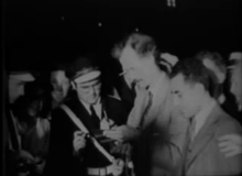 Waist high portrait of male in his forties, quite poor quality, taken before sunrise, wearing a light colored suit. Man in uniform to his right, onlooker at right.