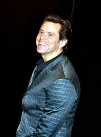 A Caucasian with dark brown hair and brown eyes, in front of a black background. He is wearing a chequered blue blazer and black shirt