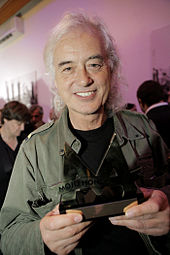 A colour photograph of Jimmy Page holding a Mojo Award, with other figures in the background
