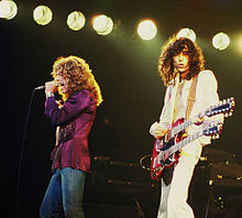 A colour photograph of Robert Plant with microphone and Jimmy Page with a double necked guitar performing on stage.
