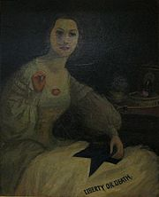 """Portrait of an attractive young woman in mid-19th century dress sewing a flag that says """"Liberty or Death"""""""