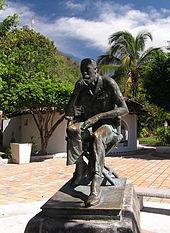 Photographie de la statut de John Huston: il est assis, pensif