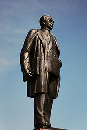 Bronze statue of Diefenbaker, taken from one side. He is depicted wearing an overcoat over a suit. He carries the Bill of Rights under his arm.