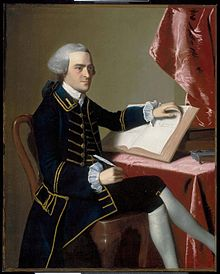 Full-length portrait of a young man seated at a table - he wears a finely tailored dark suit, knee breeches with white stockings, and a wig in the style of an English gentleman. He holds a quill pen in his right hand, and is turning the pages of a large book with the other hand.