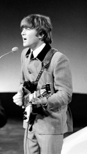 Monochrome image of John Lennon playing guitar and speaking into a microphone while wearing a grey suit.