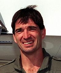 Head shot of a man, wearing a gray shirt