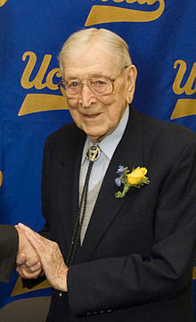 """A smiling, elderly man is shown from the waist up. He is shaking someone&squot;s hand, but that person is out of the picture. The man is wearing a dark suit with a yellow boutonniere. He has thin white hair and large glasses. He is standing in front of a blue screen that has the script """"UCLA"""" logo on it in yellow letters."""
