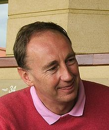 A smiling middle-aged white man with short hair, wearing a pink shirt and red pullover, looking to his left with the tip of his tongue between his lips