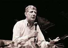 right profile, half length, of elderly man addressing an audience through a hand-held microphone