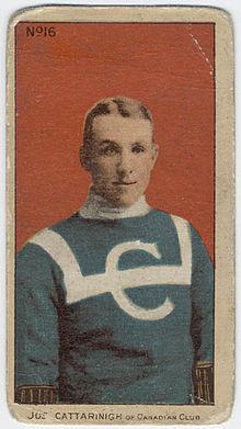 Portrait d'un jeune homme portant un chandail bleu avec col blanc, décoré par un sigle formé de la lettre C, en blanc sur la poitrine, traversée horizontalement par une bande blanche qui tourne vers le haut, à la gauche et à la droite de l'avant du chandail, et passe par-dessus les deux épaules.