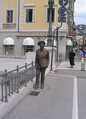 Bronze statue of Joyce standing on a sidewalk, next to a railing. Behind the statue is a street scene with pedestrians and stores.