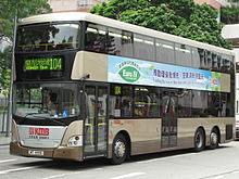 A dark tan double-decker bus with advertising-banner promoting clean environment.