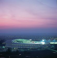 A view at twilight looking down onto a modern brightly lighted circular football stadium