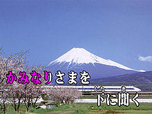 """Over a background image of Mount Fuji and a Shinkansen train two lines of Japanese text. The first half of the first line is coloured red-violet, the rest white. The text reads """"かみなりさまを 下 に聞く""""."""