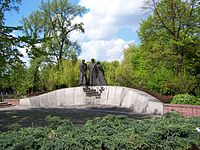 A low stone wall, curving upward. Three statues of Polish soldiers are mounted at its center. Below the statues, Text is mounted as per caption.